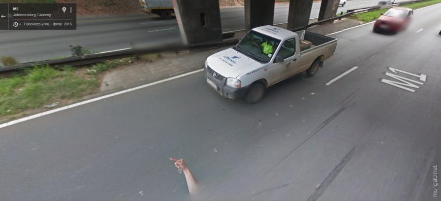 Водитель гуглокара показывает палец соседу по дорожному движению